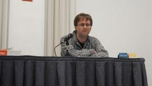 Anime Boston 2019 - Foundations of World Building - BH Pierce Sits at a table as he presents a lecture.
