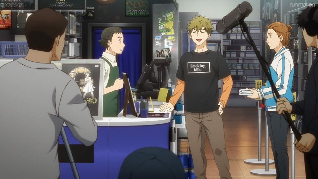 Ikebukuro West Gate Park Episode 6 that depicts two men at a counter in a video store. The man on the right smiles smugly as the man on the left stares. The two are surrounded by a camera crew.